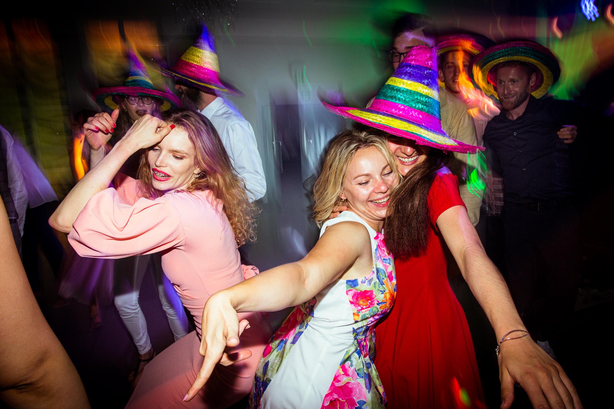 Fotoreportaż ślubny, taniec gości weselnych w kolorowych kapeluszach